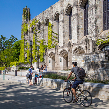 Student riding bike past Northwestern University Deering Library