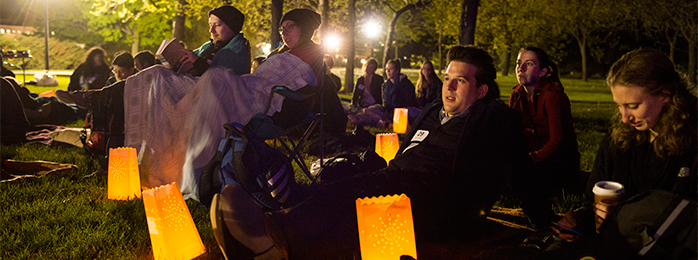 Students sitting on the lawn at night with lanterns.