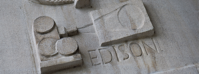 sculpture of film projector with Edison's name in stone