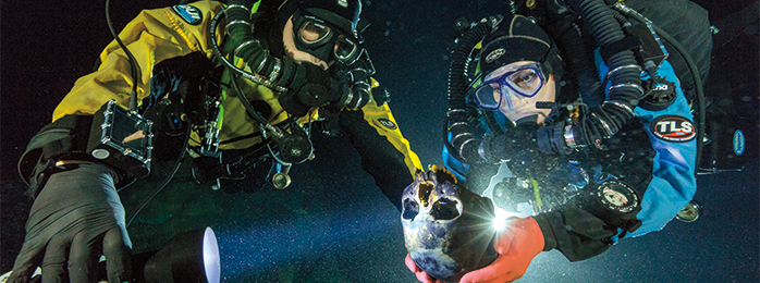 Photograph of two divers. One of the divers is holding a human skull.