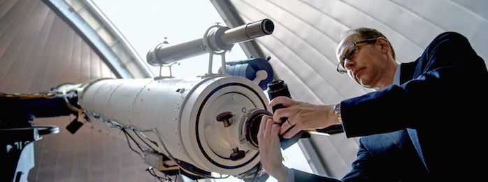 man adjusting telescope eyepiece