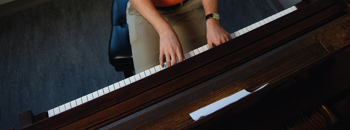 Image of a person playing a piano.