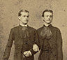 Two men in Victorian era linking arms