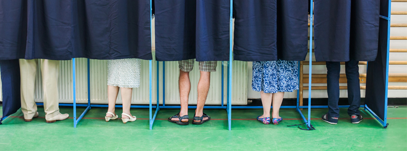 Multiple pairs of legs behind curtains at voting booths