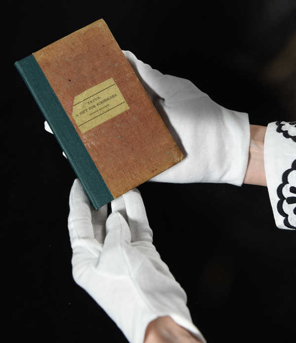 gloved hands holding an old book
