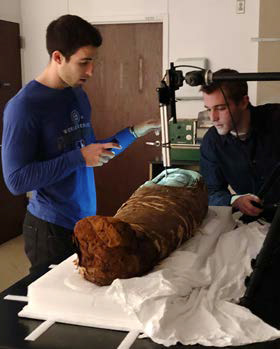 Two scientists examine the mummy and wrappings.